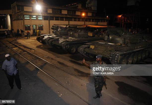 A Kenyan military officer stands guard over Soviet made T72 tanks at Mombasa port which have just been offloaded from the MV faina ship on February...