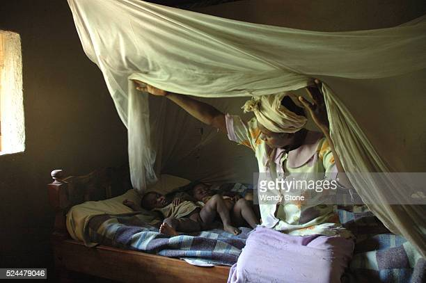 Kenyan mother and her two children sit on their bed with a mosquito net used for preventing malaria. UNICEF malaria prevention campaigns help to...