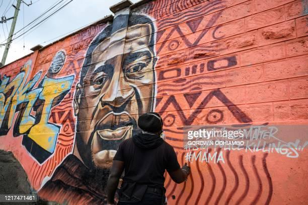 Kenyan mural artist Allan Mwangi also known as Mrdetailseven paints a graffiti mural in the Kibera slum in Nairobi on June 3 depicting the American...