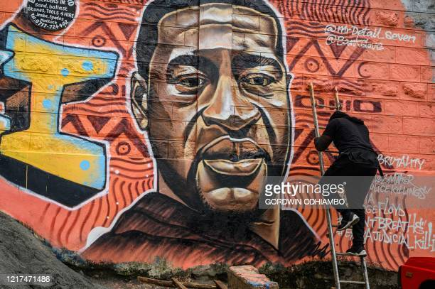 Kenyan mural artist Allan Mwangi also known as Mrdetailseven paints a graffiti mural in the Kibera slum in Nairobi on June 3 depicting the American...