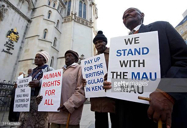 Kenyan nationals Wambugu wa Nyingi Ndiku Mutua Paulo Nzili and Jane Muthoni Mara pose for photographers outside the High Court in central London on...