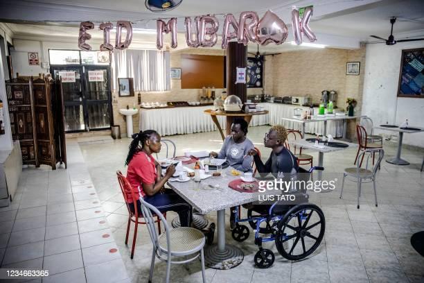 Kenyan para-rower athlete Asiya Mohammed has breakfast with athlete Miriam Nandwa and Team Kenyas physiotherapist Josephine Kaburu before starting...