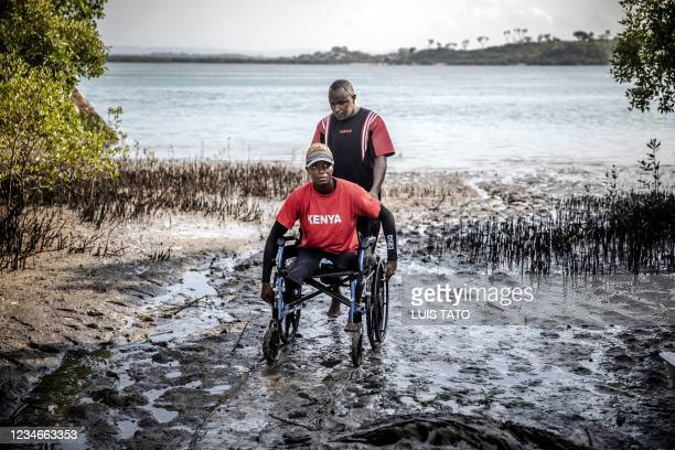 Kenyan para-rower athlete Asiya Mohammed is helped to get into the water with her wheelchair by an assistant coach during her training session at...