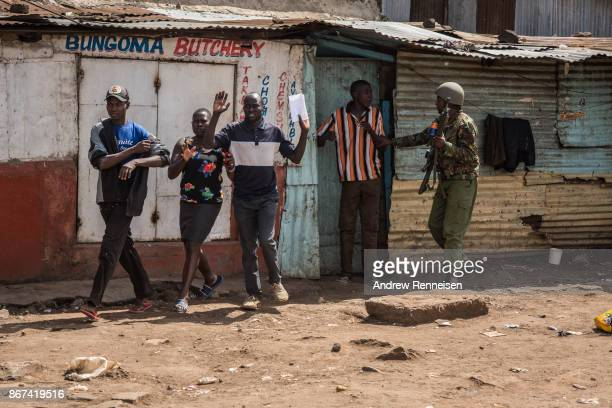 Kenyan police officer chases a group of people off a street in the Kawangware slum on October 28 2017 in Nairobi Kenya Protests continued in...