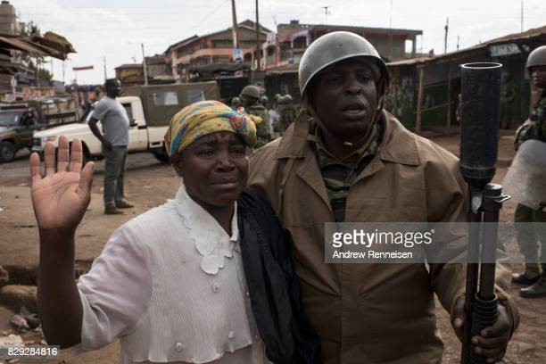 Kenyan police officer comforts a crying woman cries as police clear protestors in the Kawangware slum on August 10 2017 in Nairobi Kenya Tensions...