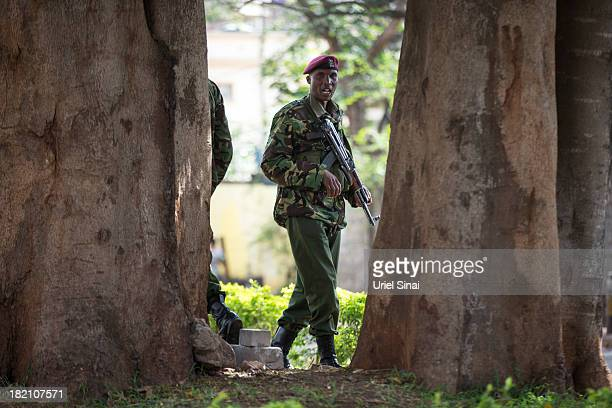 Kenyan police officer deployed near the Westgate mall stands guard on September 28 2013 in Nairobi Kenya Officals begun the task of forensic probing...