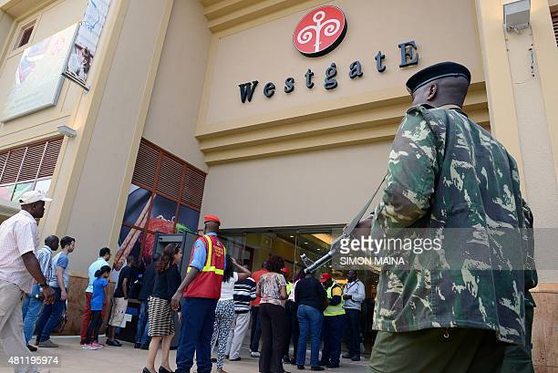 A Kenyan police officer patrols at the entrance of the Westgate shopping mall after it reopened on July 18 2015 in Nairobi Kenya's Westgate shopping...