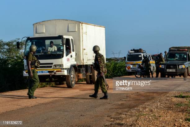 Kenyan police officers check vehicles on a road after a bus travelling from the coastal region of Lamu to the town of Malindi was ambushed by gunmen...