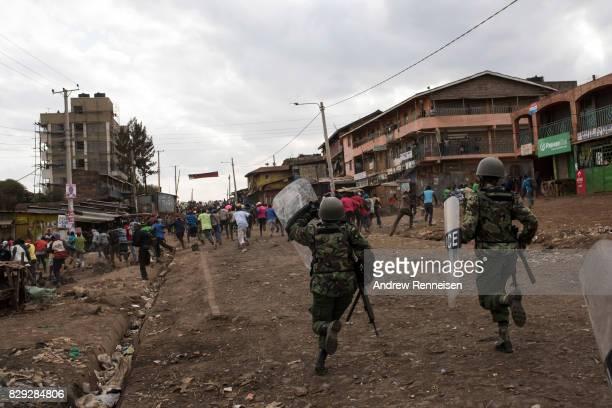 Kenyan police officers clear protestors from a street in the Kawangware slum on August 10 2017 in Nairobi Kenya Tensions remain high as rumors of...