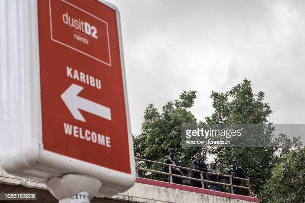 Kenyan police officers keep watch from a footbridge outside of the Dusit Hotel on January 16 2018 in Nairobi Kenya A security operation has continued...