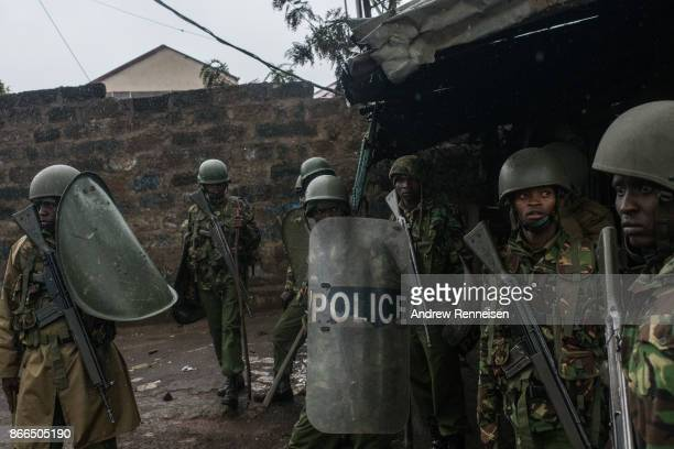 Kenyan police officers watch for rocks thrown by National Super Alliance protestors as they attempt to clear the Kibera slum on October 26 2017 in...