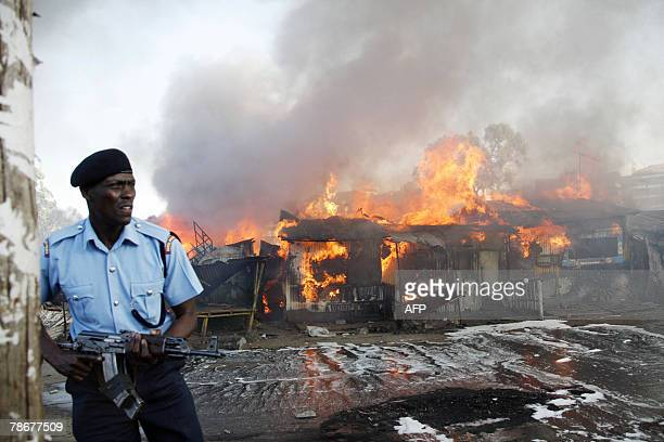 A Kenyan policeman holds his weapon at the site where supporters of presidential candidate Raila Odinga set fire to a block of houses and stores at...