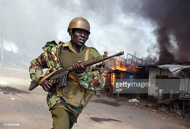 A Kenyan policeman runs past burning houses that supporters of presidential candidate Raila Odinga set fire at the Mathare slum in Nairobi 30...