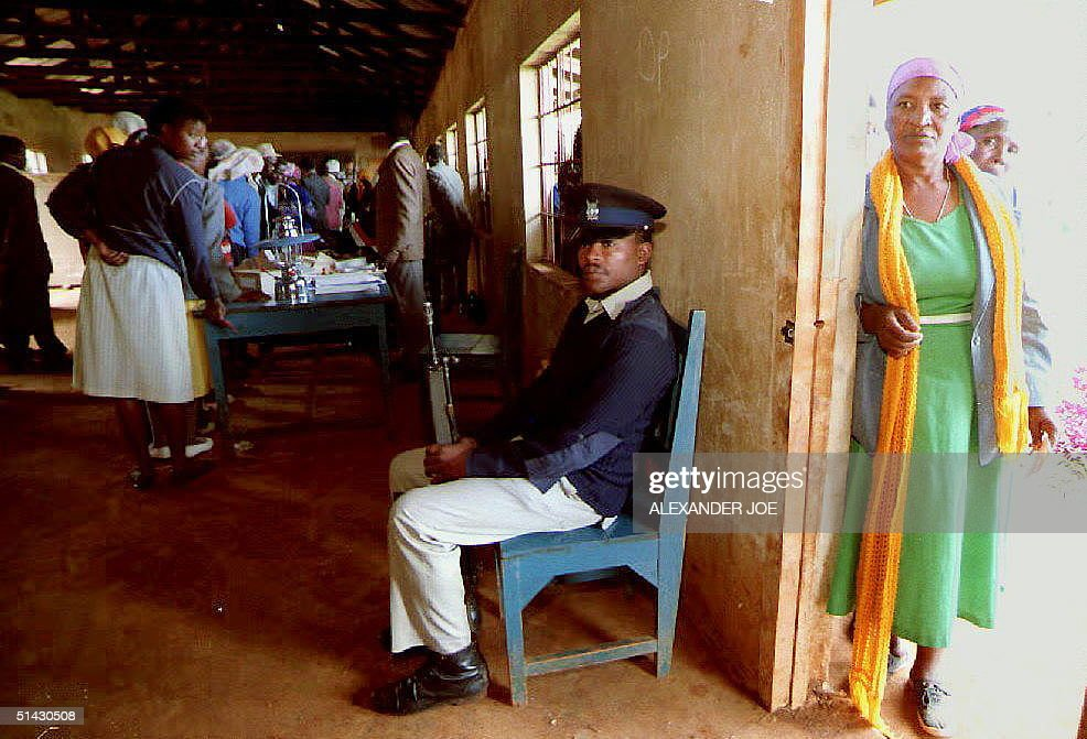 A Kenyan policeman sits in a polling station 29 De : News Photo