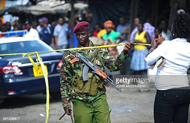 A Kenyan policeman stands at the scene of an explosion in Gikomba on the outskirts of Nairobi's business district where twin blasts claimed at least...