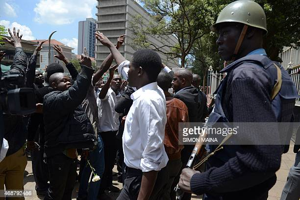 A Kenyan policeman watches as protesters march in the streets of Nairobi to demand greater national security on April 7 ahead of a candlelight vigil...