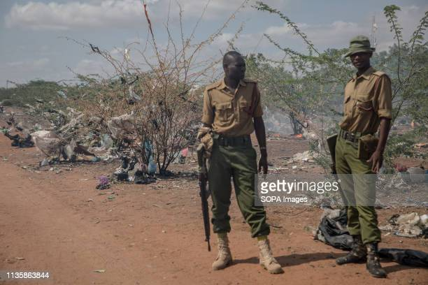 Kenyan policemen seen standing amid burning rubbish in the refugee camp. Dadaab is one of the largest refugee camps in the world. More than 200,000...
