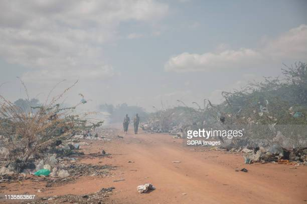 Kenyan policemen seen walking amid burning rubbish in the refugee camp. Dadaab is one of the largest refugee camps in the world. More than 200,000...