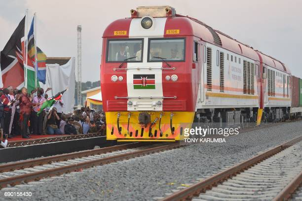 Kenyan President Uhuru Kenyatta flags off a cargo train as it leaves the container terminal on its inaugural journey to Nairobi at the port of the...