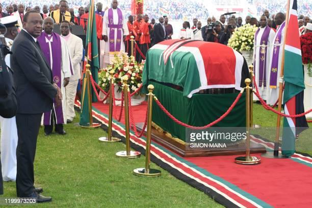 Kenyan President Uhuru Kenyatta stands next to the coffin of late former Kenya President Daniel Arap Moi draped in the Kenya national flag during a...