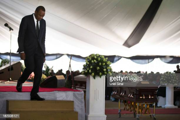 Kenyan President Uhuru Kenyatta walks down from the stage past his nephew's coffin at the funeral service for his nephew Mbugua Mwangi and his...