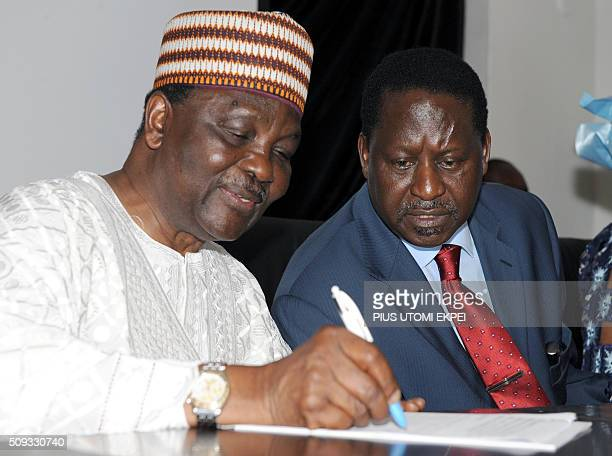 Kenyan Prime Minister Raila Odinga watches former Nigeria's military Head of State General Yakubu Gowon writting down notes during the 25th Silver...