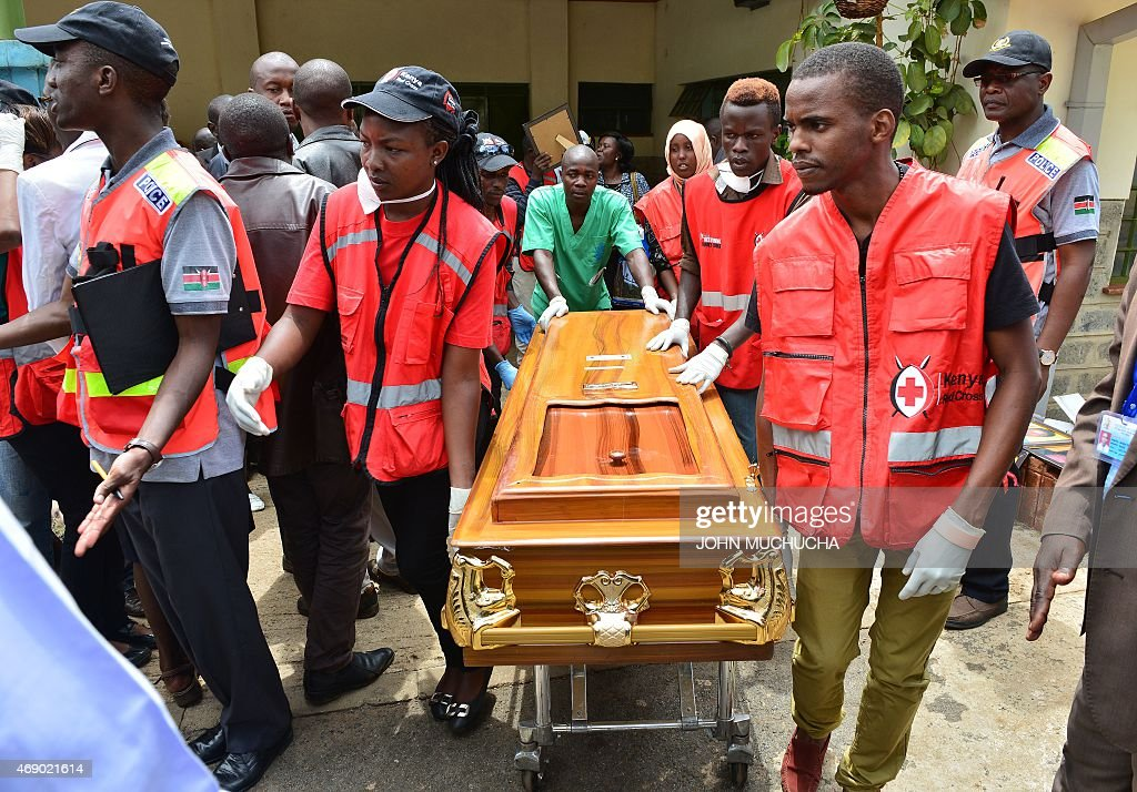 Kenyan Red Cross staff help move the coffin of a victim ...