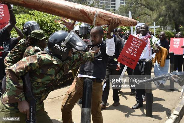 Kenyan rights activist Boniface Mwangi is roughed by police officers during a peacefull demonstration against police killings within recent...