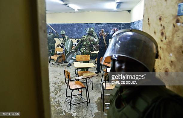 Kenyan riot police clash with students inside a classroom in Nairobi University on May 20 2014 The students were protesting against a controversial...