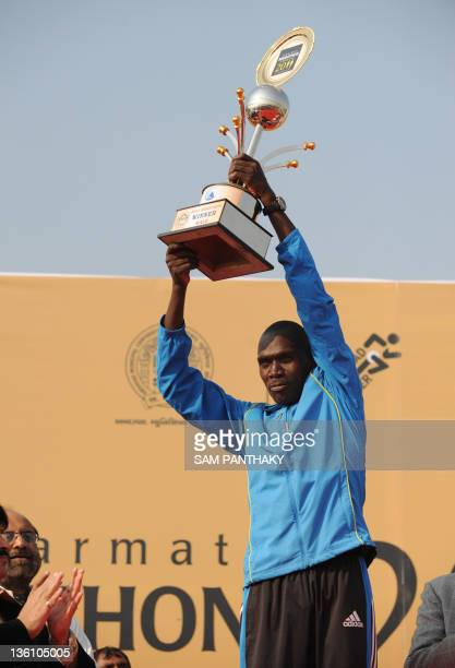 Kenyan runner Philemon Rotich holds up his trophy after winning the Sabarmati Marathon 2011 in Ahmedabad on December 25 2011 Rotich finished first in...