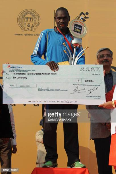Kenyan runner Philemon Rotich poses with his winning cheque and trophy after the Sabarmati Marathon 2011 in Ahmedabad on December 25 2011 Rotich came...