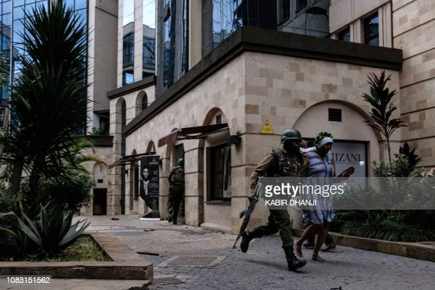 TOPSHOT Kenyan security forces evacuate people after a bomb blast at DusitD2 hotel in Nairobi Kenya on January 15 2019 A huge blast followed by a gun...