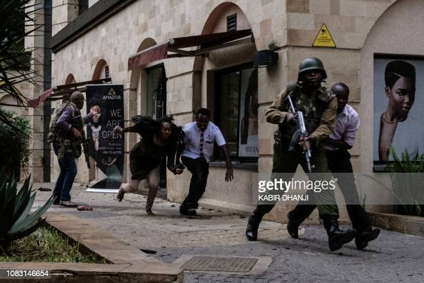 TOPSHOT Kenyan security forces help people to escape after a bomb blast at DusitD2 hotel in Nairobi Kenya on January 15 2019 A huge blast followed by...