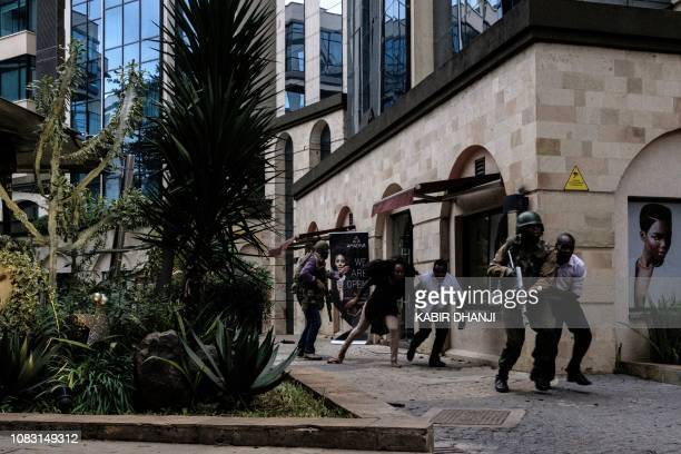 Kenyan security forces help people to escape after a bomb blast at DusitD2 hotel in Nairobi Kenya on January 15 2019 A huge blast followed by a gun...