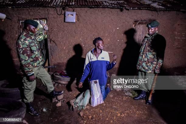 TOPSHOT Kenyan security officers arrests a man selling alcohol door to door during curfew hours in Kisumu western Kenya on March 29 2020 The Kenyan...