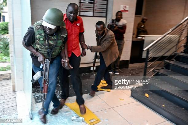 Kenyan security officers rescue a survivor as a gunfight was underway following a blast at a hotel and office complex in Nairobi on January 15 2019 A...