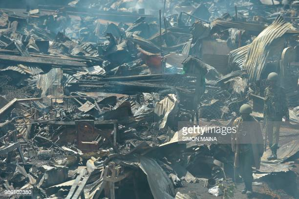 Kenyan security officers walk past the smouldering debris following a fire that gutted the timber dealership at the Gikomba market and nearby homes...