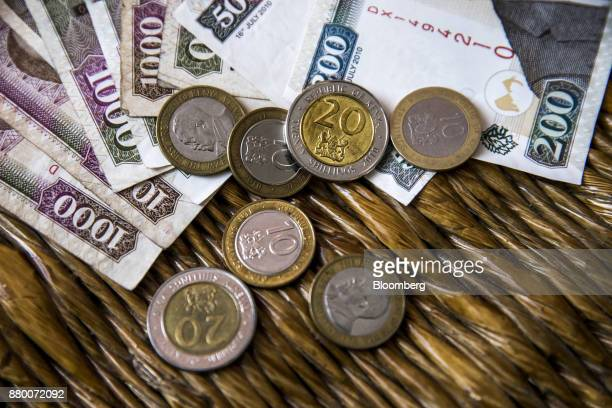 Kenyan shilling banknotes and coins sit arranged at a market stall in Mombasa Kenya on Thursday Nov 23 2017 The countrys Treasury has already cut...