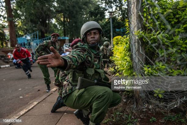 Kenyan soldier urges people to take cover after hearing gunfire coming from the Dusit Hotel complex on January 15 2018 in Nairobi Kenya A current...