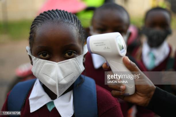 Kenyan students from Our Lady of Mercy Primary School Nairobi South have their temperature measured as they resume in-class learning after a...