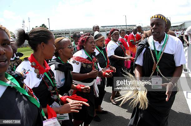 Kenyan traditional dancers wave as the plane carrying the Pope prepares to depart on November 27 2015 in Nairobi on its way to Kampala Uganda