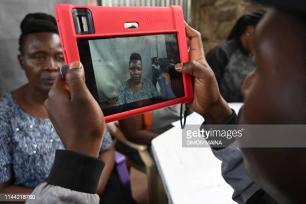A Kenyan woman looks at a biometric camera prior to register for the Huduma Namba on May 2019 in Nairobi Huduma Namba is conducted by National...