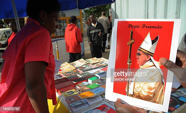 A Kenyan woman looks at a potrait of Pope Francis on sale outside the Holy Basilica in Nairobi on March 24 2013Today marked Palm Sunday in the...