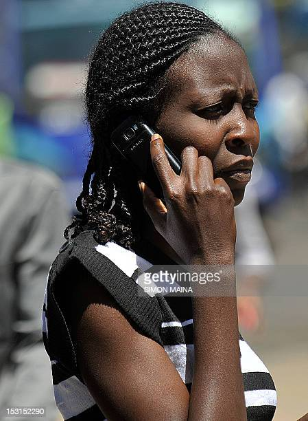 A Kenyan woman talks on her cellphone on October 1 2012 in Nairobi Kenya has confirmed that a switchoff of counterfeit mobile phones will take place...