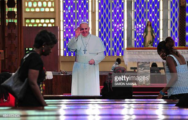 A Kenyan woman walks past a cardboard cutout of Pope Francis at the Holy Family Basilica on October 27 2015 in Nairobi during a lunch time prayer...