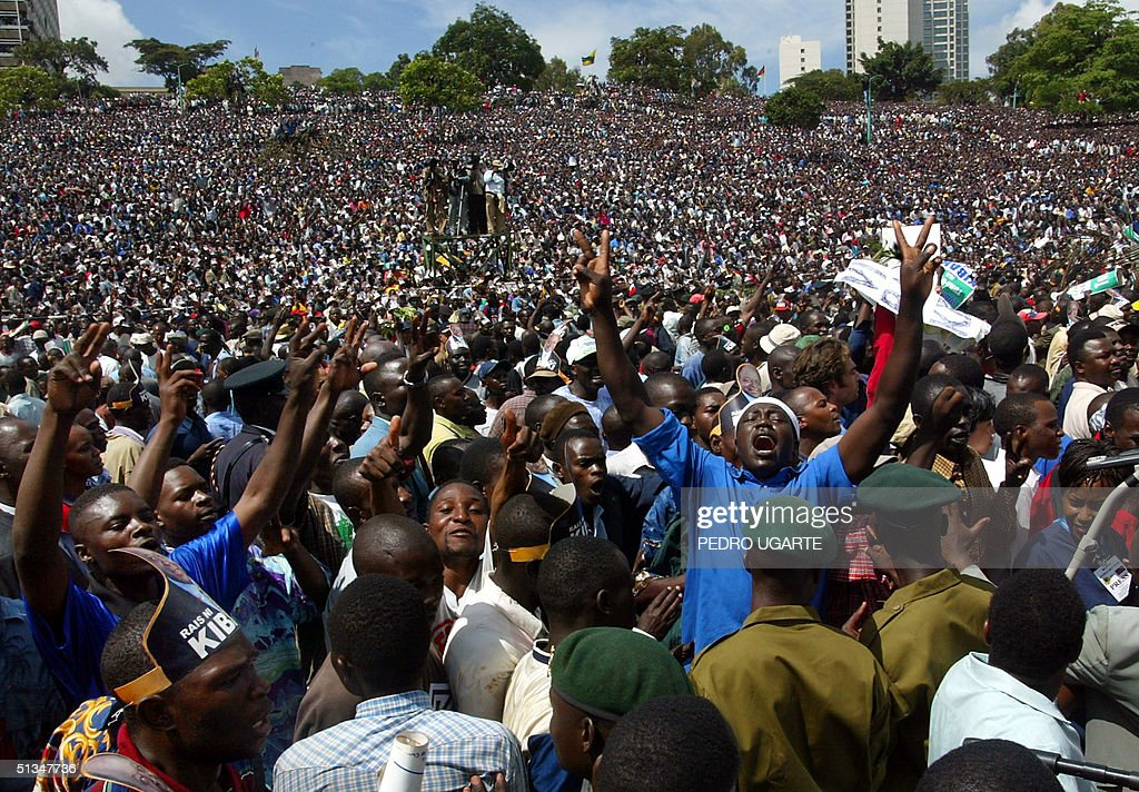 Kenyans gather for the swearing in ceremony of newly elected president Mwai Kibaki in Nairobi 30 December 2002. A million jubilant Kenyans turned out in a Nairobi park to witness the inauguration of President Mwai Kibaki, voicing hopes that decades of rampant corruption, croneyism and grinding poverty could soon be a thing of the past.