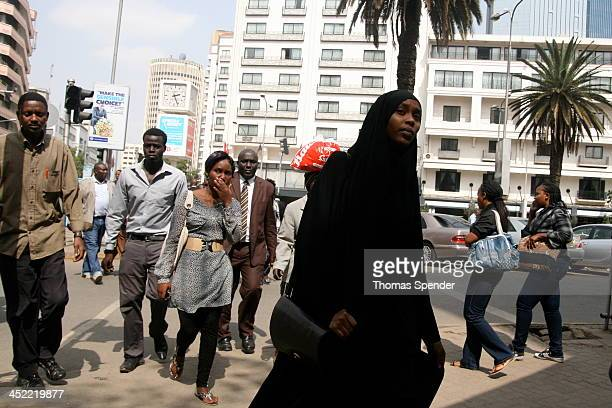 Kenyans including a woman in a black hijab cross a street in Nairobi's busy Central Business District.