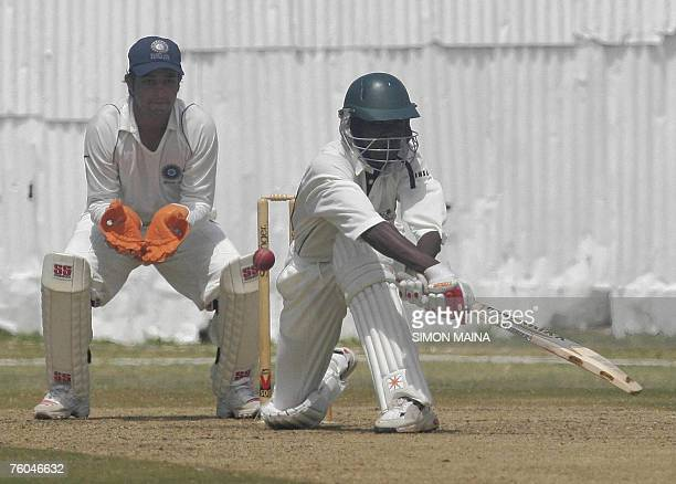 Kenya's batsman Alex Obanda hits against Indian bowler Pragyan Ojha as wicketkeeper Mahesh Rawat 10 August 2007 waits the catch during their threeday...
