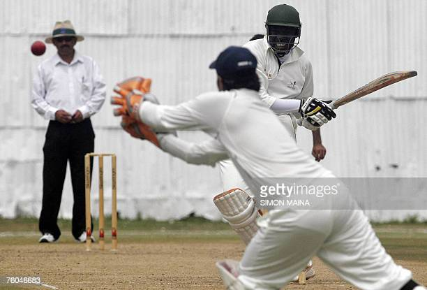 Kenya's batsman David Obuya watches as India team A wicketkeeper Mahesh Rawat catches him before being out for 30 runs during their three day match...