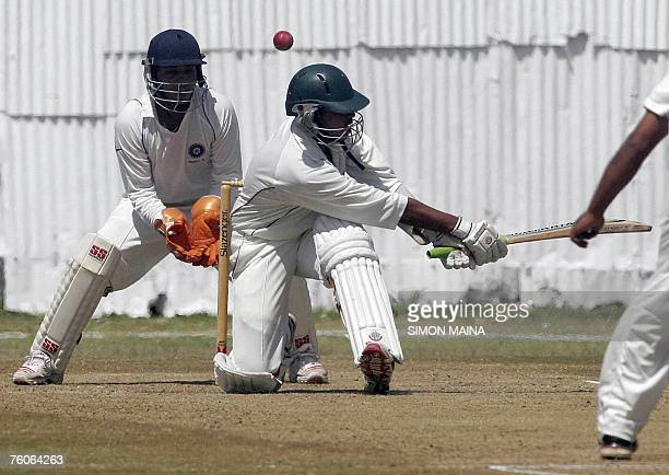 Kenya's batsman Hiren Varaiya makes a swing as he misses a delivery from India's bowler Rajesh Pawar as wicket keeper Mahesh Rawat waits for the...